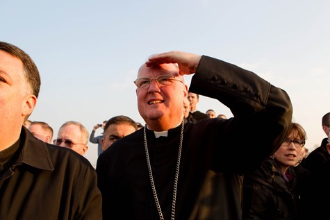 New York Cardinal Timothy Dolan watches as the helicopter carrying Pope Benedict lifts off from the Vatican grounds February 28.  Pilot photo/Gregory L. Tracy