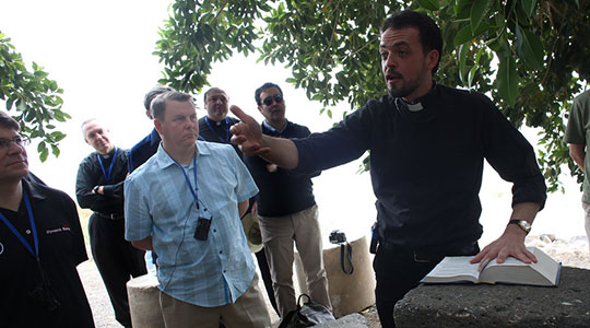 Fr. David Barnes listens as the local guide, Fr. Francesco, speaks of the biblical significance of where they are. (George Martell/TheGoodCatholicLIfe.com)