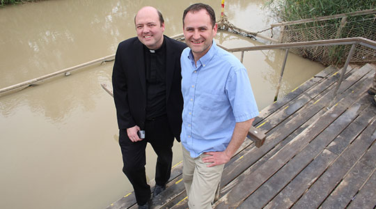 Fr. Michael Harrington, left, and Fr. Dan Hennessey stand by the Jordan River. (George Martell/TheGoodCatholicLife.com)