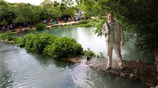 Fr. Dan Hennessey stands beside the source of the Jordan River in Caesarea Philippi. (Photo by George Martell/theGoodCatholicLife.com)