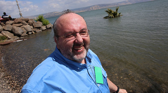 Fr. Paul Soper standing beside the Sea of Galilee (George Martell/TheGoodCatholicLIfe.com)